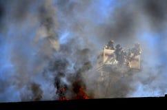 Bombeiros na cubeta da escada observando o fogo Imagens de Stock Royalty Free