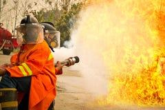 Bombeiros no fogo de combate da ação durante o treinamento Foto de Stock Royalty Free