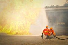 Bombeiros no fogo de combate da ação durante o treinamento Fotografia de Stock Royalty Free