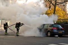 Bombeiros que extinguem o fogo do carro foto de stock