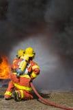 2 bombeiros que pulverizam a água na luta contra o incêndio com o fogo e o smo escuro Fotografia de Stock