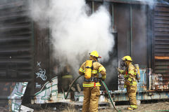 Bombeiros que trabalham para põr para fora o incêndio Foto de Stock