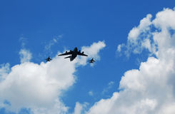 Bomber and fighter planes. A big bomber and two fighter planes flying in a cloudy sky Stock Photos