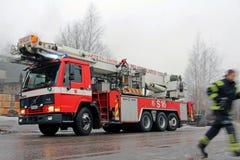 Bombero acometido y coche de bomberos de Volvo FL12 que llega la escena del fuego Fotos de archivo libres de regalías