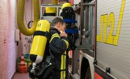 Bombero con el cilindro de oxígeno en el coche de bomberos Imágenes de archivo libres de regalías
