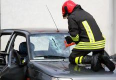 Bombero con los guantes del trabajo mientras que rompe un parabrisas del coche al rele Imágenes de archivo libres de regalías