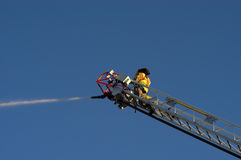 Bombero en el agua del aerosol del carro de escala en el fuego Fotos de archivo