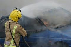 Bombero en el fuego del coche Fotos de archivo libres de regalías