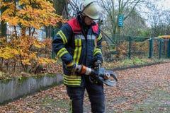 Bombero en la acción con las herramientas de la emergencia Imagen de archivo