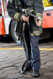 Bombero Holding Water Hose en el parque de bomberos Imagen de archivo