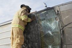 Bombero Inspecting un coche estrellado Fotografía de archivo libre de regalías