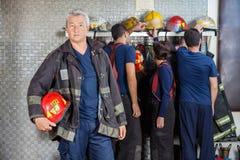 Bombero maduro confiado que se coloca en el parque de bomberos Fotografía de archivo