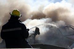 Bombero que apaga el fuego Fotos de archivo