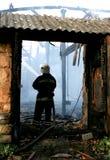 Bombero que apaga un fuego de la casa Imagenes de archivo
