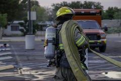 Bombero que consigue la manguera de bomberos de aparejo Imagen de archivo