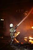 Bombero que lucha un fuego foto de archivo