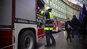 Bombero que pone el equipo en el firetruck, trabajo peligroso, responsabilidades metrajes