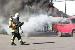 Bombero y coche ardiente Imagen de archivo libre de regalías