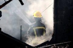Bombero y humo en casa Foto de archivo