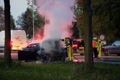 Bomberos cerca de una ruina del coche del quemar foto de archivo