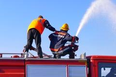 Bomberos en la acción de la lucha contra el fuego Foto de archivo