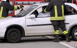 Bomberos en la acción después del accidente de carretera Imagenes de archivo
