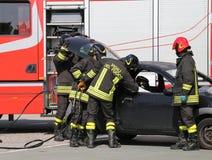 Bomberos en la acción durante el accidente de carretera Imágenes de archivo libres de regalías