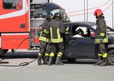Bomberos en la acción durante el accidente de carretera Fotos de archivo libres de regalías