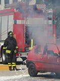 Bomberos en la acción durante un accidente de carretera Imágenes de archivo libres de regalías