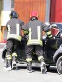 Bomberos en la acción durante un accidente de carretera Fotos de archivo libres de regalías