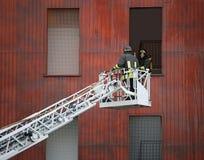 Bomberos en la acción durante una práctica en la casa del fuego Foto de archivo