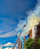 Bomberos en una escala que extingue el fuego Imagen de archivo libre de regalías