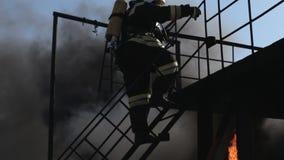 Bomberos en uniforme y máscaras arriba y abajo del almacen de metraje de vídeo