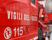 bomberos grandes del significado de las palabras VIGILI DEL FUOCO en el firetruck rojo Imagenes de archivo