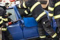Bomberos que abren las puertas de coche con las tijeras hidráulicas Fotos de archivo libres de regalías