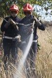 Bomberos que apagan el fuego del arbusto Fotos de archivo libres de regalías