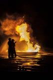 Bomberos que apagan un fuego foto de archivo