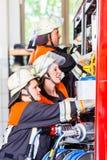 Bomberos que atan la manguera en la manguera que pone el vehículo Imagen de archivo