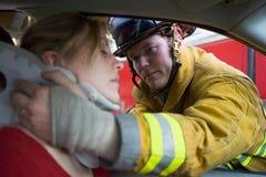 Bomberos que ayudan a una mujer dañada en un coche Fotos de archivo libres de regalías