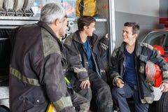 Bomberos que conversan en camión en el parque de bomberos Fotografía de archivo libre de regalías