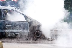 Bomberos que extinguen un coche que arde y quemado imagenes de archivo