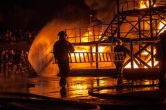 Bomberos que llevan una escalera durante un ejercicio contraincendios Fotografía de archivo