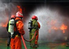 Bomberos que luchan el fuego Foto de archivo libre de regalías