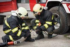 Bomberos que preparan las tijeras hidráulicas para uso del rescate Imágenes de archivo libres de regalías