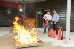 Bomberos que realizan el entrenamiento controlado del fuego imagen de archivo