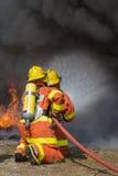 2 bomberos que rocían el agua en la lucha contra el fuego con el fuego y el smo oscuro Foto de archivo libre de regalías