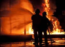 Bomberos que usan la manguera del agua en el fuego que rabia Imagen de archivo