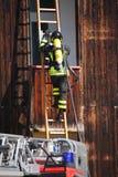 Bomberos valientes con el fuego del tanque de oxígeno durante un ejercicio llevado a cabo Imagenes de archivo