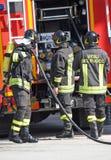 Bomberos valientes con el fuego del tanque de oxígeno durante un ejercicio llevado a cabo Fotos de archivo libres de regalías