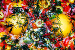Bombez les oeufs dans une poêle avec le poivre, les olives et les verts Photo stock